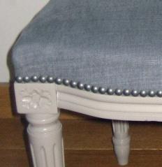 Détail de la finition avec des clous décoratifs d'une chaise de style Louis XVI